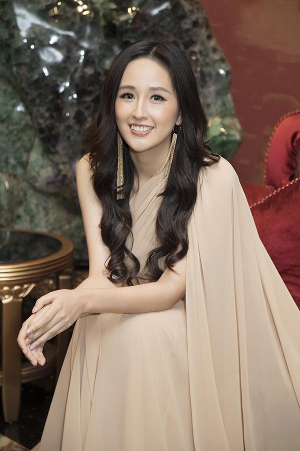 Người đẹp phối trang phục với khuyên tai dáng dài và mái tóc xoăn nhẹ.