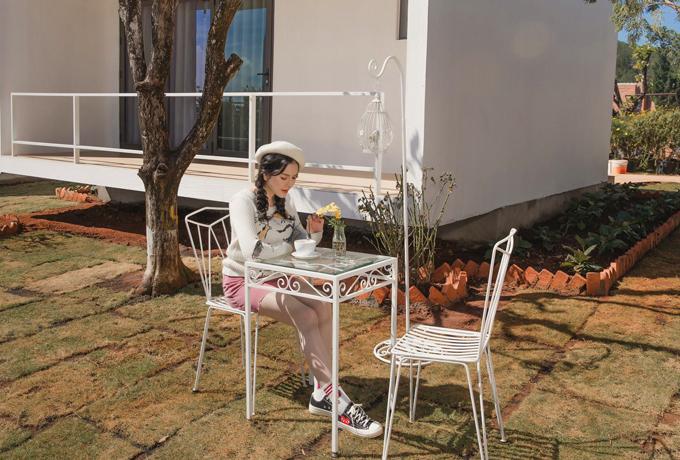 Cô diện trang phục xì tin, chậm rãi ngồi uống trà trước sân một căn biệt thự trong resort.