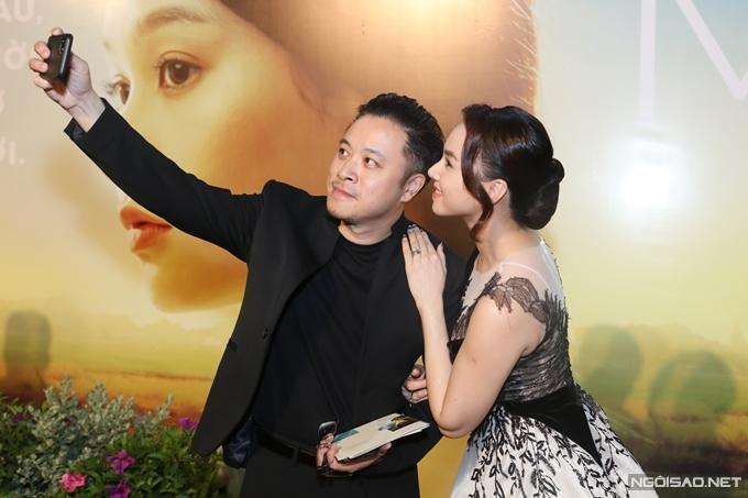 Victor Vũ cầm điện thoại selfie với vợ.