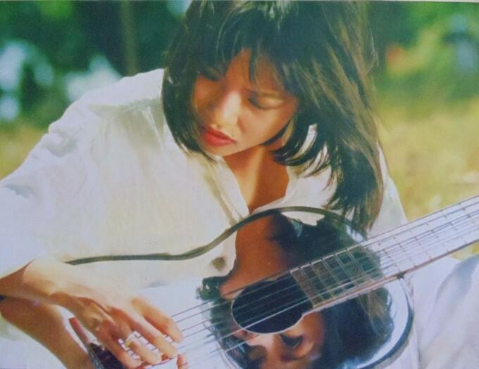 Phương Thanh ôm đàn, làm mẫu chụp ảnh bìacho một tạp chí năm 1999.