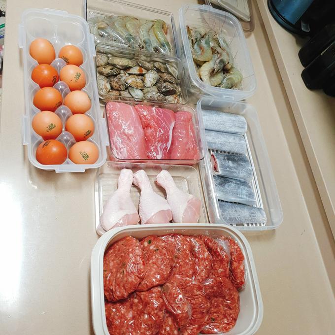 Để giữ thực phẩm tươi ngon, mẹ 9X tìm hiểu kỹ về thời gianbảo quản được từng loại nguyên liệu trong tủ lạnh. Chất đạm có thể trữ đông lâu nhất 6 tháng, với rau củ là 1 tuần. Khi mua các thực phẩm tươi sống, giàu đạm như tôm, cá, Dịu sẽ sơ chế sạch sẽ rồi mới đặt vào hộp. Thịt cá được cắt khúc vừa chiều dài của hộp. Khi đã rải hết các khúc cá mà hộp vẫn còn nhiều diện tích, Dịu sẽ dùng màng thực phẩm để phân tách không gian hộp, rải thêm các khúc cá lên bên trên, giúp các khúc cá không bị dính, dễ lấy.