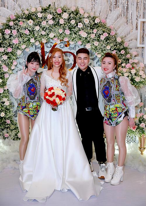 Khi đón khách và thực hiện nghi lễ cưới, cô dâu chọn lựa kiểu váy dáng A, có đính kết đá nơi thân trên và thân dưới xòe nhẹ, làm từ satin.