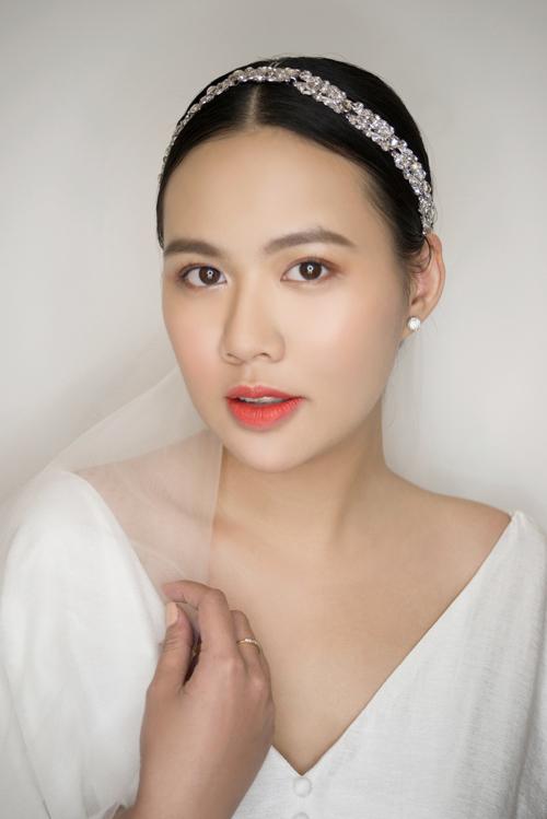 Đôi môi được phủ son cam cháy, giúp lôi cuốn ánh nhìn. Cô dâu có thể kết hợp phụ kiện đơn giản là bờm đá và búi tóc thấp.
