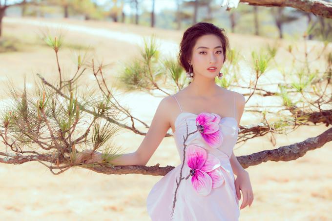 Váy dạ hội trang trí hoa mộc lan tôn màu rực rỡ được êkíp của hoa hậu Lương Thuỳ Linh chọn lựa để thực hiện bộ ảnh tại thành phố ngàn thông.