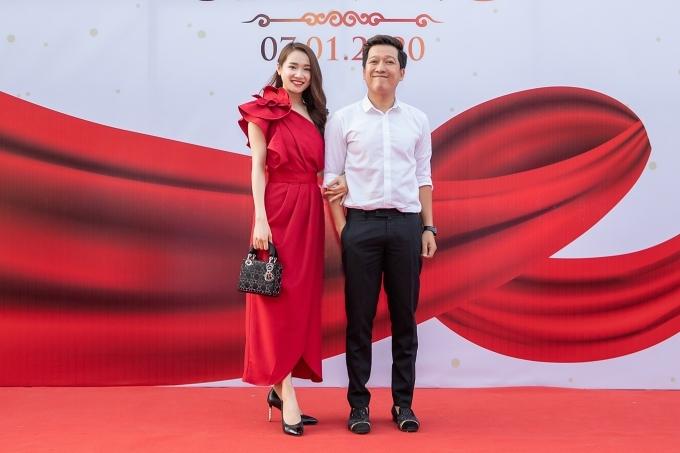 Nhã Phương diện váy màu đỏ nổi bật, khoác tay ông xã Trường Giang tại lễ khai trương nhà hàng.