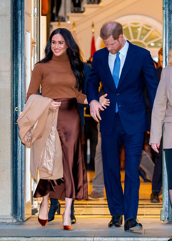 Nữ công tước xứ Sussex giơ tay ra trước cho chồng nắm khi rời tòa nhà Canada House chiều muộn 7/1. Ảnh: Daily Mirror.