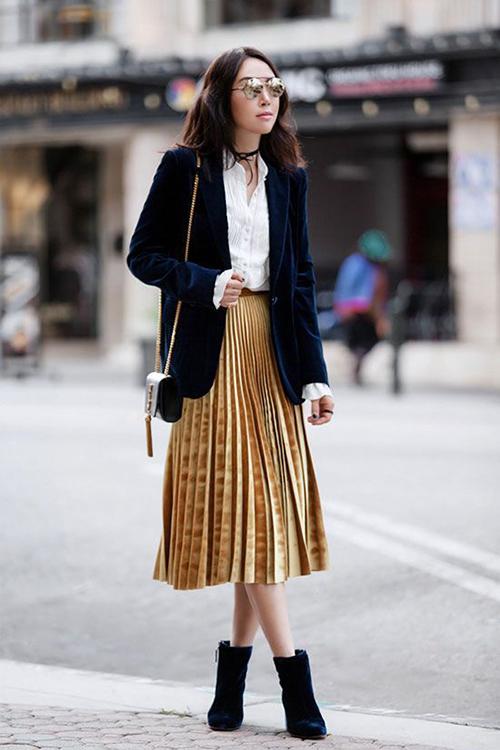 Áo nhung bóng bẩy được mix cùng chân váy xép ly chất liệu metalic mang vẻ đẹp của sự hào nhoáng.