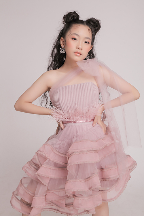 Váy hồng nude được chăm chút về phom dáng với cách kết hợp chân váy nhiều tầng, áo quây được tô điểm lông vũ tiệp màu. Ngoài ra, dải voan lụa mềm mỏng được thắt nơ tinh tế sẽ khiến các bé gái xinh đẹp như nàng công chúa khi tham gia tiệc tất niên, đón năm mới cùng ba mẹ.