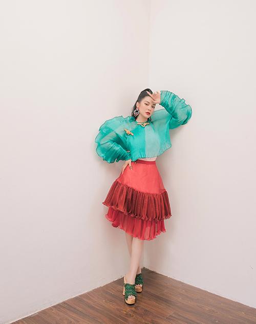 Áo tay phồng lấy cảm hứng từ thân trên của áo dài truyền thống được Liy Chen kết hợp với váy ngắn xếp tầng hiện đại. Nữ diễn viênthể hiện khả năng mix đồ táo bạo khi phối áo xanh bạc hà với chân váy đen và guốc mộc xanh lá cây đậm.