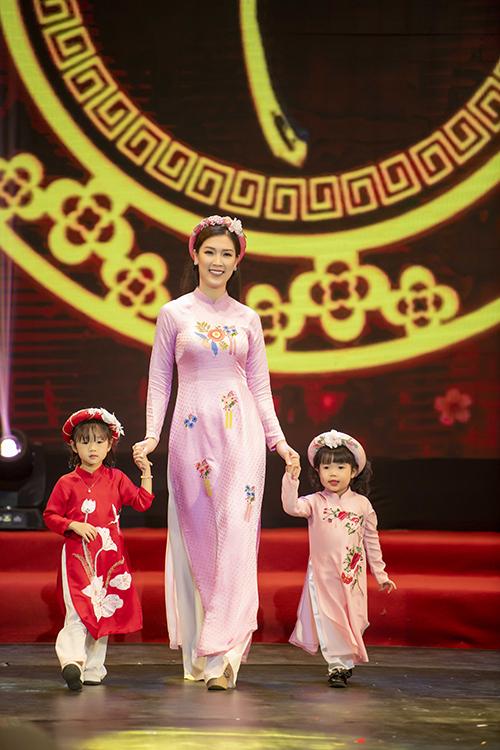 Phí Thùy Linh dắt theo hai mẫu nhí khi đi catwalk. Các bé rất thích thú khi sải bước trên sân khấu.