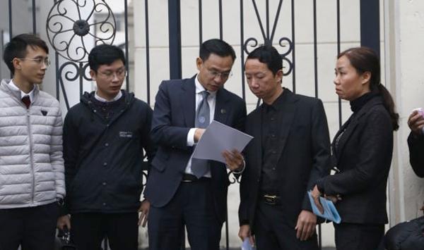 Anh Lê Văn Sơn (thứ hai từ phải sang), đại diện gia đình nạn nhân, trao đổi với luật sư trước phiên tòa. Ảnh: Nguyễn Ngoan.
