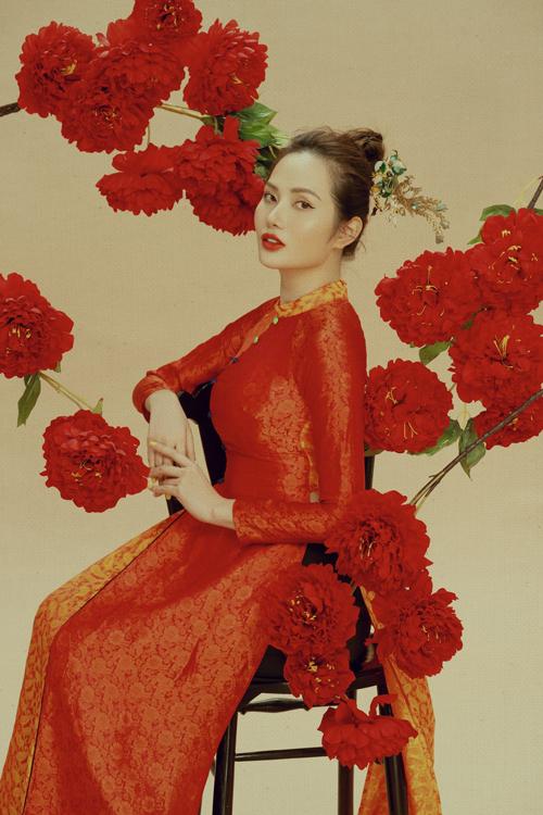 Tóc búi rối đơn giản và phù hợp với các nàng năng động được chọn lựa cho Diệu Linh khi diện áo dài cổ thấp phối màu đỏ cam cuốn hút.