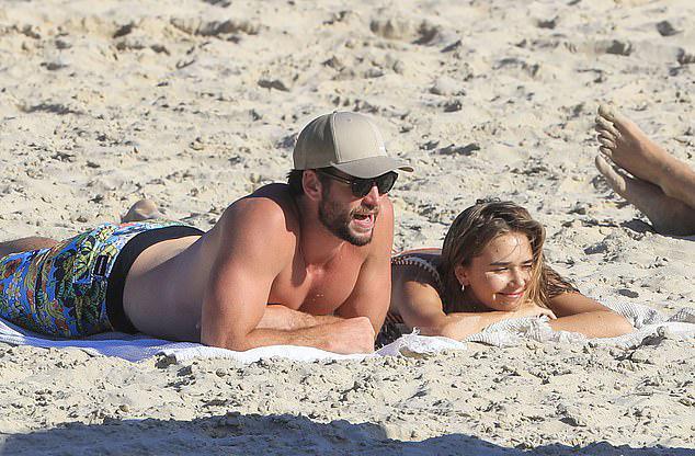 Cặp đôi hạnh phúc nằm phơi nắng và tâm tình trên bãi biển.