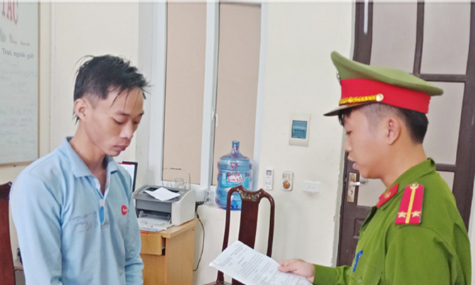 Nghi can Hạnh (bên trái) nghe cảnh sát đọc lệnh bắt. Ảnh: C.A