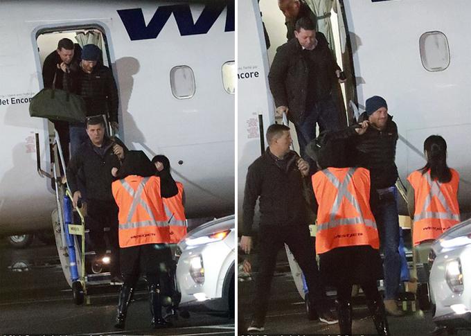 Harry khoác chiếc túi xách tươi cười bước xuống máy bay ở Canada tối 20/1. Ảnh: Christ Bott.