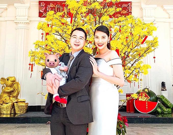 Vợ chồng Lan Khuê - Tuấn John bế con trai đầu lòng chụp ảnh trước hiên nhà. Đây là năm đầu tiên cặp trai tài gái sắc lên chức bố, mẹ.