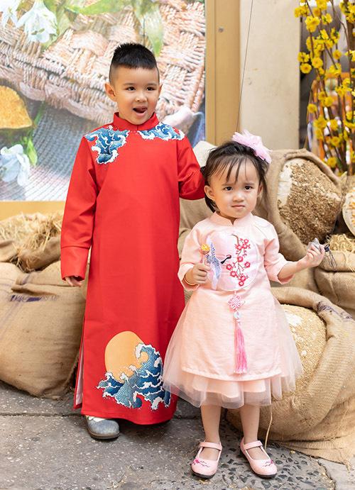 Bé Voi tỏ ra chững chạc khi diện áo dài đi chơi xuân trong khi em gái xinh xắn, đáng yêu với một cây hồng.