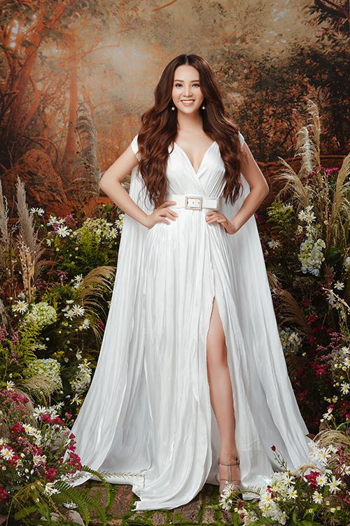Người đẹp diện phong cách nữ thần với mái tóc xoăn nhẹ để ngôi giữa, váy trắng đính áo choàng thướt tha và khuyên tai ngọc trai.