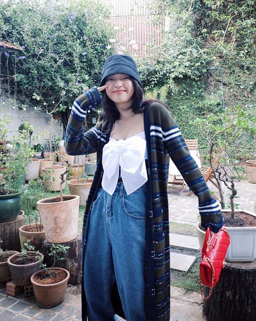 Vẫn diện áo chiếc nơ của Chanel nhưng khi đi du lịch Châu Bùi lại chọn cardigang dáng dài và jeans cổ điển để mix đồ.