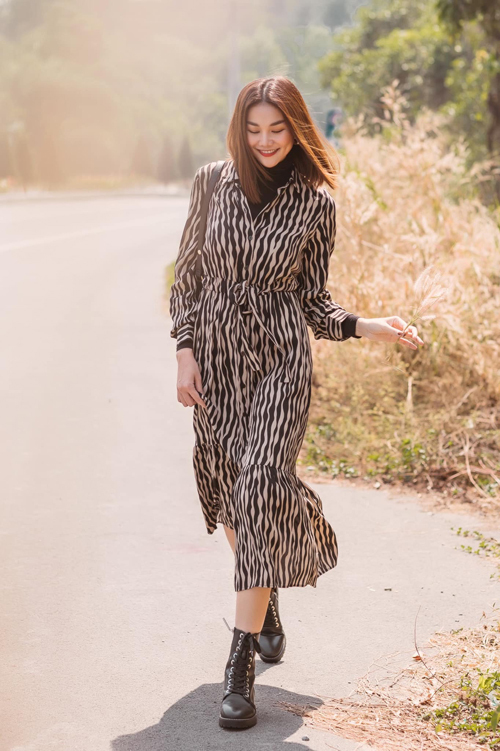 Thanh Hằng trẻ trung với cách mix váy sơ mi họa tiết trắng đen cùng áo cổ lọ ton-sur-ton cùng bốt cao cổ.