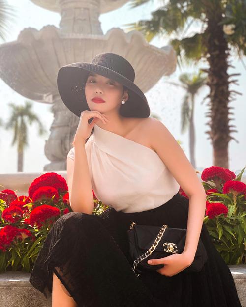 Lan Khuê sang trọng với cách mix màu trắng đen cho nón rộng vành, váy bất đối xứng. Túi Chanel kiểu dáng cổ điển được người đẹp chọn lựa để hoàn thiện set đồ.