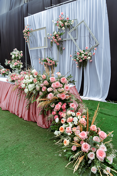 Phía bên ngoài nơi làm lễ là bàn tiếp tân được tô điểm với các bông hồng Đà Lạt, cỏ lau, giúp cô dâu, chú rể và dàn khách mời có những hình ảnh đẹp mắt.