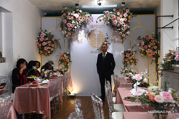 Không gian làm lễ tại nhà cô dâu mang tông hồng - sắc màu cô dâu yêu thích. Tân nương chọn hoa hồng, các khung sắt mỹ thuật để tân trang diện mạo ngôi nhà. Bàn chữ nhật, ghế tàng hình (ghost-chair) giúp không gian tiếp đón khách trở nên sang trọng.