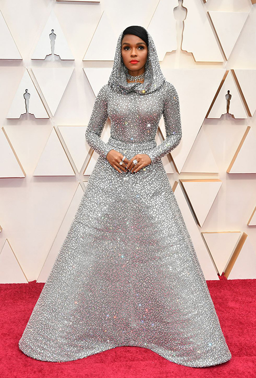 Luôn biết cách khiến bản thân trở nên khác biệt, nữ ca sĩ 34 tuổi Janelle Monae diện đầm ánh bạc kèm mũ trùm đầu do nhà mốt Ralph Lauren sáng tạo. Trang phục đặt hàng riêng này được đính thủ công 168.000 viên pha lê Swarovski lấp lánh.