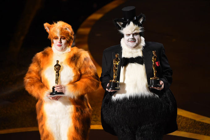 Hai ngôi saoRebel Wilson (trái) và James Corden mặc bộ trang phục giống trong phimCats của họ để bê tượng Oscar ra sân khấu.