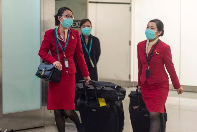 Tiếp viên hàng không Cathay Pacific đeo khẩu trang kín khi rời sân bay. Ảnh: CNN.