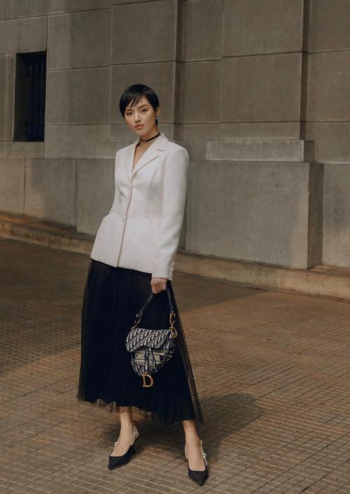 Khánh Linh diện nguyên set đồ Dior. Cô chọn mẫu bar jacket với đường chiết eo tinh tế để phối cùng chân váy xòe kết hợp chất liệu vải lưới chấm bi tông đen.