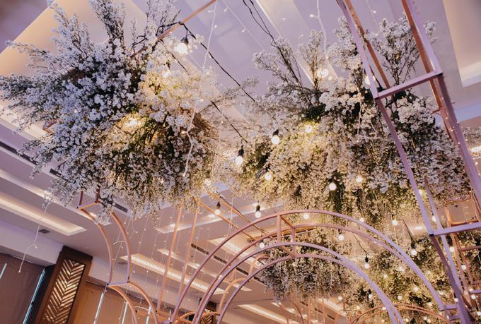 Phía trên của dàn khung được tô điểm bởi các loài hoa mà cô dâu, chú rể yêu thích, giúp xóa đi vẻ cứng nhắc do những khối kim loại mang lại.