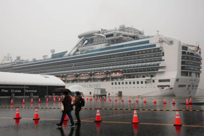 Du khách đi bộ gầntàu Diamond Princess đã bị cách ly tại cảng Yokohama vàosáng chủ nhật. Ảnh AP