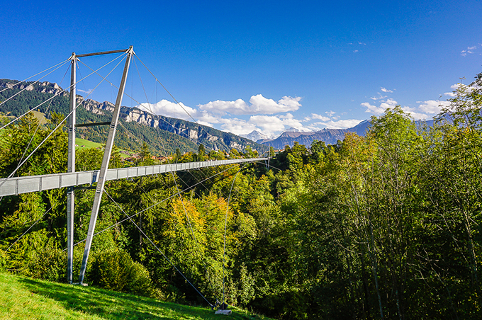 Panorama Bridge Sigriswil [Panoramabrücke Sigriswil] is a 340 m long pedestrian suspension bridge that stretches over the Gummi Gorge [Gummischlucht] at 180 m height and connects the two villages Aeschlen und Sigriswil in the Canton of Bern, Switzerland. It is located between Thun and Interlaken at the Thun Lake and the bridge allows for a spectacular view on this lake and the Bernese Alps. This bridge is understood as the center piece of the circular walking trail around the Thun Lake [Panorama Rundweg Thunersee].