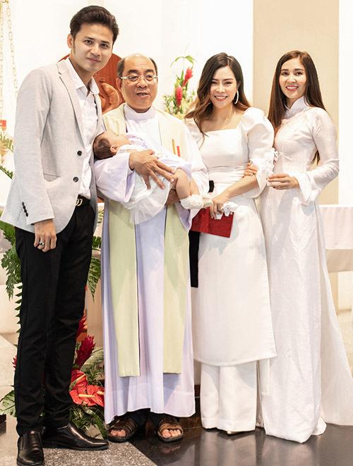 Vợ chồng Vũ Ngọc Ánh cùng một người thân chụp ảnh kỷ niệm cùng vị linh mục sau khi hoàn thành nghi thức rửa tội cho con gái.