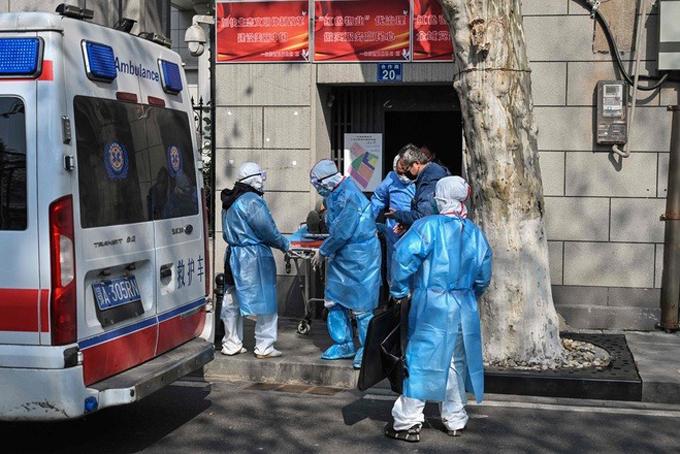 Các nhân viên y tế ở Vũ Hán đến nhà dân đưa người nhiễm virus corona đi. Ảnh: Reuters.