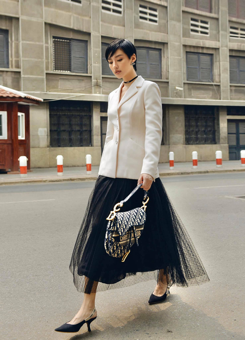 Khánh Linh sang trọng và kiểu cách với nguyên set đồ đồ Dior. Thiết kế chân váy xoè và chiếc bar jacket có đường chiết eo tinh tế giúp người mặc gợi cảm hơn.