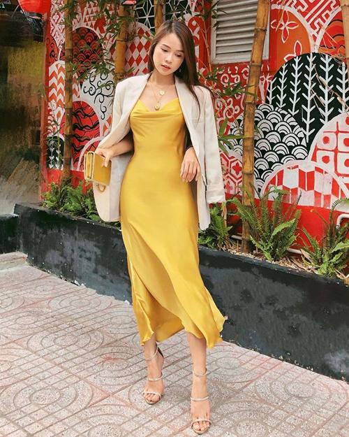 Những cô nàng có vóc dáng mảnh mai có thể tham khảo cách phối váy lụa vàng cùng áo khoác màu trung tính như của Sam.