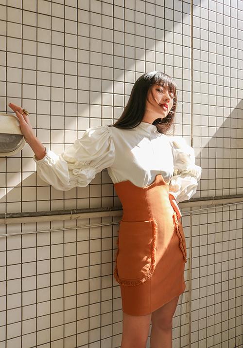 Thanh Vy tôn vóc dáng với thiết kế áo blouse trắng đi kèm chân váy ôm gam cam đào - một trong những gam màu nằm trong top hot trend 2020.