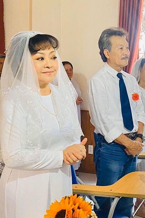 Danh ca Hương Lan diện áo dài trắng, cài voan cô dâu và mỉm cười hạnh phúc bên ông xã Quốc Toản.