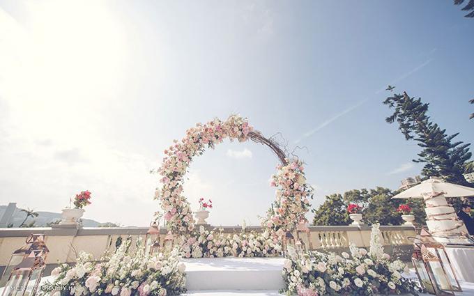 Không gian cưới ngoài trời của uyên ương mang tông trắng, hồng từ màu sắc của nghìn đóa hoa. Cánh cổng hoa hình tròn còn có ý nghĩa biểu tượng về tình yêu vĩnh cửu, không có điểm dừng.