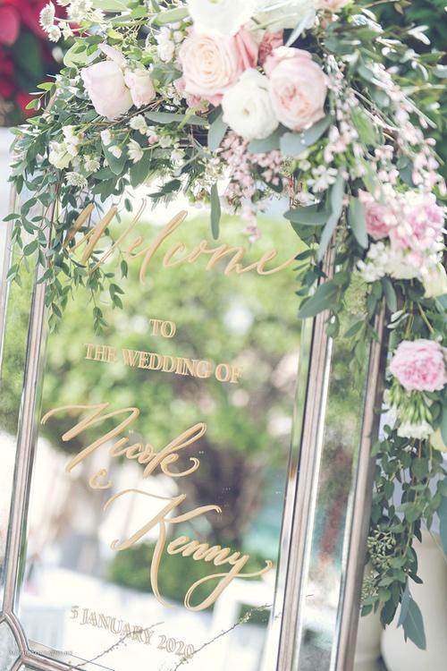 Bảng welcome đám cưới mang phong cách hiện đại, tô điểm bởi hoa tươi,chữ được dán trên kính tráng gương.