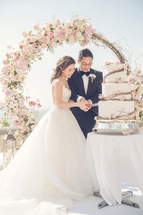 Cả hai vợ chồng lựa chọn bánh cưới trắng 3 tầng, điểm nhành cây và hoa hồng.