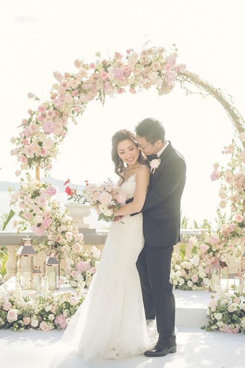 Mẫu đầm được đắp ren dọc thân. Cô dâu chọn lựa hoa cưới bó tròn kết từ hồng.