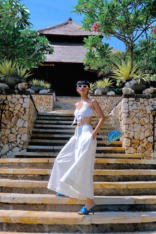 Sandal Bottega Veneta tông xanh bắt mắt được Khánh Linh phối ton-sur-ton cùng clutch da ánh kim khi diện nguyên cây trắng khoe eo thon sexy.