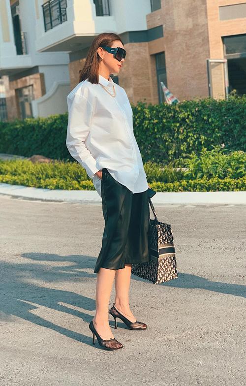 Thanh Hằng thanh lịch nhưng không kém phần cách tính với street style mùa hè gồm áo sơ mi phom rộng, quần ống lửng màu tương phản, túi Dior và mắt kính, giày cao gót hợp mốt.