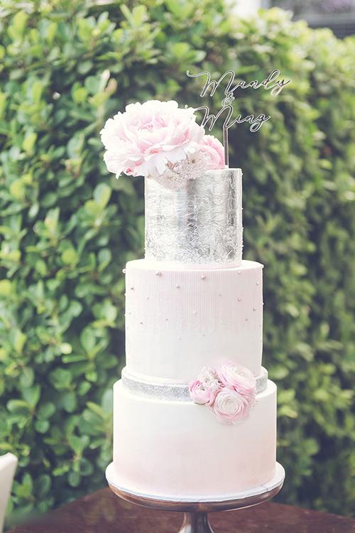 Bánh cưới của uyên ương được tô điểm bởi hoa tươi, các hạt đường giả ngọc trai khắp mặt bánh.