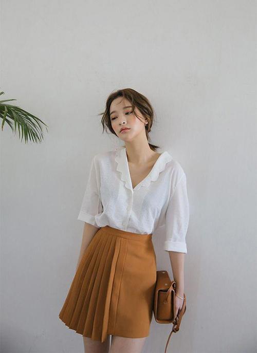 Phong cách mang hơi hướng cổ điển với áo sơ mi vintage phối cùng chân váy tông cam nâu hot trend mùa thời trang 2020.