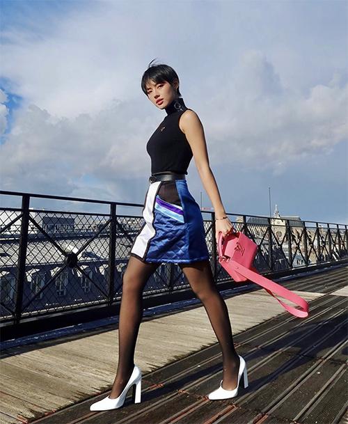 Sắc hồng nữ tính, blue đúng trend được Khánh Linh phối hợp nhịp nhàng trên bộ cánh dạo phố gồm áo ốmats nách, chân váy và túi Louis Vuitton.