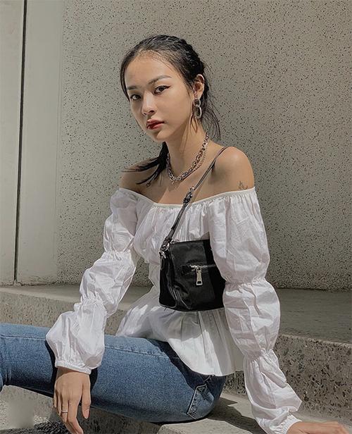 Phong cách cổ điển và quen thuộc ngày hè được Phí Phương Anh thể hiện một cách cuốn hút qua lối mix áo trễ vai đi cùng jeans xanh và shoulder bag.